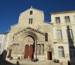 Late afternoon winter sunlight warms the front of Arles' church on the main square.